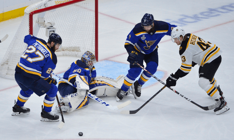 St. Louis Blues and Boston Bruins players battle for the puck